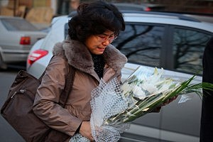 A North Korean woman cries as she arrives at the North Korea embassy to mourn the death of North Korean leader Kim Jong-il