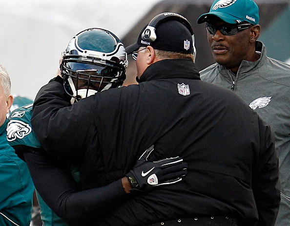 Michael Vick #7 of the Philadelphia Eagles hugs head coach Andy Reid