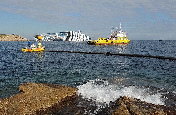 Floating barriers are laid out to prevent pollution of the coast from the stricken cruise ship Costa Concordia