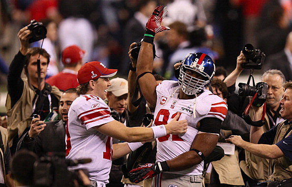 Eli Manning #10 of the New York Giants celebrates with Justin Tuck #91 after defeating the New England Patriots to win the Super Bowl XLVI