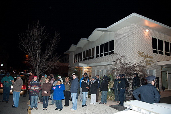 Fans outside the Whigman Funeral Home in Newark await the arrival of a hearse carrying Whitney Houston's body.