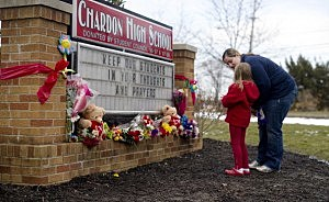 Angela May and her daughter, Eleanore, 5, of Chardon place flowers on the sign outside Chardon High School in Chardon, Ohio
