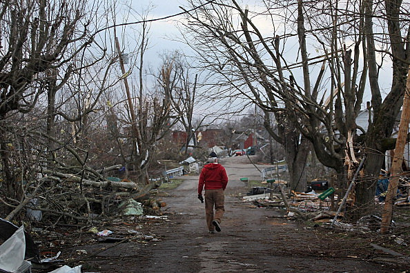A volunteer walks down a tornado-ravaged street March 3, 2012 in Henryville, Indiana.