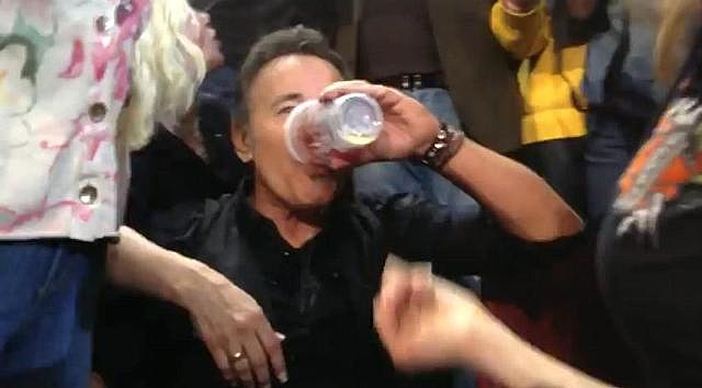 Bruce chugs a beer in the audience