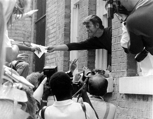 English singer David Bowie leans out of a window to pass autographs to fans during a visit to, Brixton, London, 6th July 1989