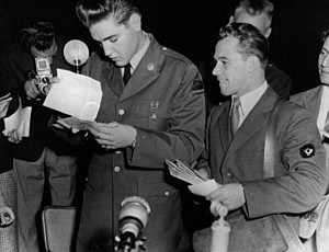 Rock 'n' roll star Elvis Presley (1935 - 1977), now a GI, receives his first bundle of mail at the Friedberg US Army base in Germany