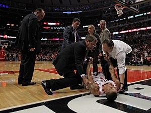Derrick Rose #1 of the Chicago Bulls is lifted off of the court as coach Tom Thibodeau (L) watches after suffering a knee injury against the Philadelphia 76ers