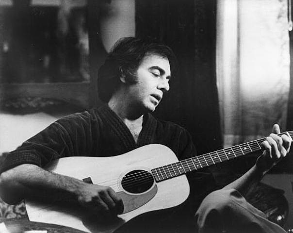 American pop singer-songwriter Neil Diamond relaxes with his guitar. Diamond is shortly to make his film debut in a remake of 'The Jazz Singer'.