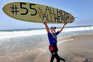 "Fred Hodges shows a surfboard he decorated during a ""paddle-out"" in honor of Junior Seau in Oceanside, California."