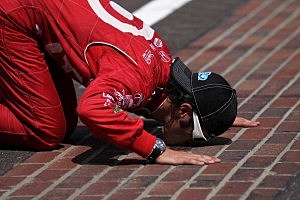 Dario Franchitti of Scotland, driver of the #50 Target Chip Ganassi Racing Honda, kisses the yard of bricks in celebration of winning the IZOD IndyCar Series 96th running of the Indianapolis 500 mile race