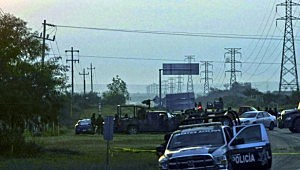 Police block a highway early Sunday morning where dozens of bodies were found.