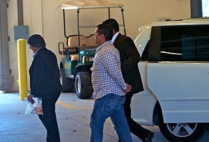 George Zimmerman (C) is escorted by police as he returns to Seminole County Jail