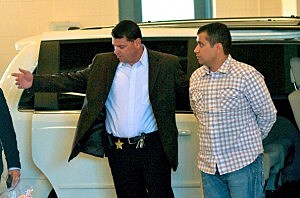 George Zimmerman (R) is escorted out of a van in to the Seminole County Jail