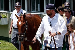 Trainer Doug O'Neil walks with I'll Have Another during a press conference outside of barn two on June 8, 2012 in Elmont, New York.
