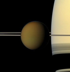 The colorful globe of Saturn's largest moon, Titan, passes in front of the planet and its rings in this true color snapshot from NASA's Cassini spacecraft.  (NASA.gov)