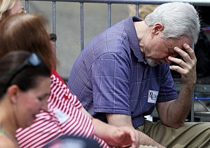 A Romney supporter prays for victims of the Colorado shooting at a Mitt Romney appearance in Bow, NH