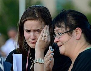 Dara Anderson (L) and Monique Anderson cry during a candelight vigil
