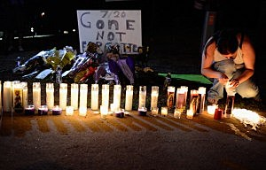 A woman lights candles at a makeshift memorial for victims of the Colorado theater shooting.
