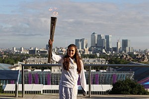 Natasha Sinha, 15, holds the Olympic torch aloft in front of a view of central London at the Observatory in Greenwich Park