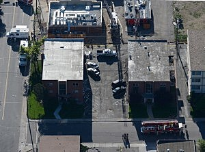Seen from the air, police and fire fighters surround the booby-trapped apartment of suspect James Holmes
