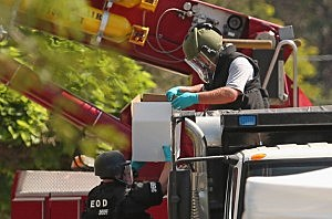 Federal, state and local law enforcement agents and explosives experts load boxes of improvised explosive devices from James Holmes' apartment into a sand-filled dump truck