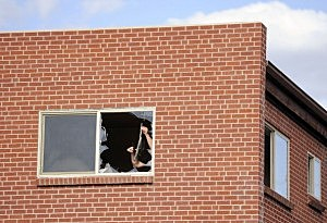A law enforcement official removes broken glass from the window of the apartment of James Holmes,