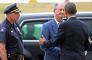 President Barack Obama (R) is greeted by Aurora Police Chief Dan Oates (L) and Aurora Mayor Steve Hogan