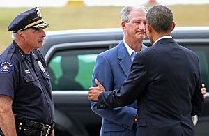 President Barack Obama (R) is greeted by Aurora Police Chief Dan Oates (L) and Aurora Mayor Steve Hogan