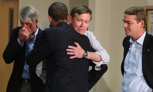 President Barack Obama embraces Colorado Gov. John Hickenlooper as Sen. Mark Udall (D-CO) (L) and Sen. Michael Bennet (D-CO) look on during a visit to the University of Colorado Hospital