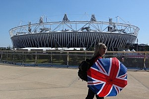 A woman walks by Olympic Stadium before the rehearsal of opening ceremony at Olympic Park
