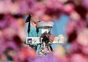 A wooden cross with the name and sailor's cap of shooting victim John Larimer, the Navy intelligence officer from Crystal Lake, Illinois, is viewd through a heart-shaped wreath at a makeshift memorial across the street from the Century 16 movie theater