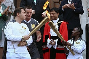 Torchbearer Rhyania Blackett-codrington (R) passes on the Olympic flame to comedian David Walliams (L), before setting off from Islington Town Hall on day 69 of the London 2012 Olympic Torch Relay