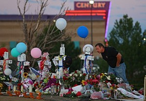 People visit a memorial setup across the street from the Century 16 movie theatre