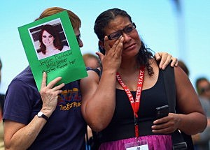 P.K. McKenzie (L) comforts Stella Ojeda while holding a picture of her former classmate Jessica Ghawi