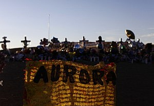 Crosses and a banner are lit by the morning light at a memorial across the street from the Century 16 movie theatre