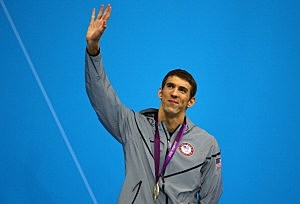 Silver medallist Michael Phelps of the United States waves to the crowd from the podium during the medal ceremony for the Men's 200m Butterfly final