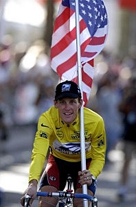Lance Armstrong of USA and the US Postal team cycles round the Champs Elysees with the USA flag after winning the 1999 Tour de France