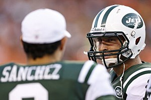 Tim Tebow #15 of the New York Jets looks at teammate Mark Sanchez
