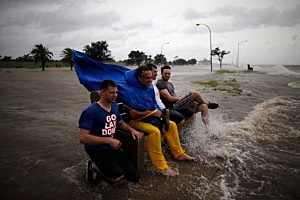 A group of men sit on a bench at the edge of Lake Pontchartrain