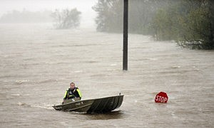 A rescue boat passes a partially submerged stop sign during Hurricane Isaac  in Braithwaite, Louisiana.