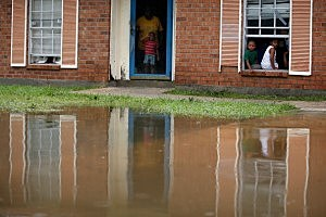 Residents sit in their house near flood waters from Hurricane Isaac  in Reserve, Louisiana.
