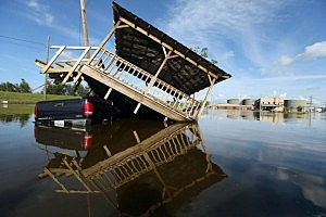 A partially submerged truck and gazebo are seen in Hurricane Isaac's flood waters with a flooded chemical plant in the background in in Braithwaite, Louisiana