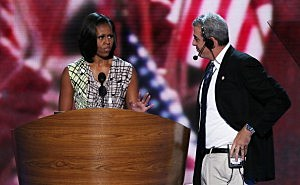 First lady Michelle Obama stands at the podium on stage with stage manager David Cove for a soundcheck during preparations for the Democratic National Convention