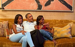 President Barack Obama and his daughters, Malia (L) and Sasha, watch Michelle Obama's address at the White House