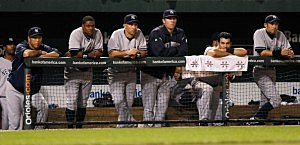 Members of the New York Yankees look on from the dugout