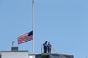 White House employees walk down from the rooftop after lowering the national flag to half-staff
