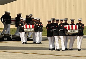 Transfer cases are carried into a hangar during the Transfer of Remains Ceremony for the return of Ambassador Christopher Stevens and three other Libyan embassy employees