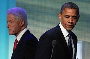 President Barack Obama (R) walks past former U.S. President Bill Clinton at the Clinton Global Initiative meeting
