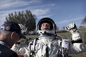 Felix Baumgartner of Austria celebrates after he lands at the desert during the second manned test flight for Red Bull Stratos