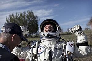 Felix Baumgartner of Austria celebrates after he lands at the desert during the second manned test flight for Red Bull Stratos
